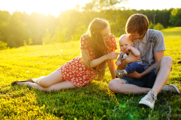 Happy and young  family resting on the beautiful lawn