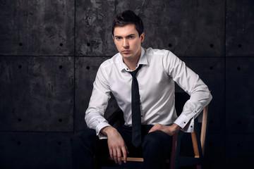 Strong man on chair exudes confidence, Studio portrait