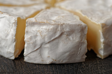 Head of brie cheese cut in pieces
