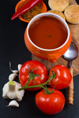 Fresh spiced tomato soup with garlic, pepper and bread