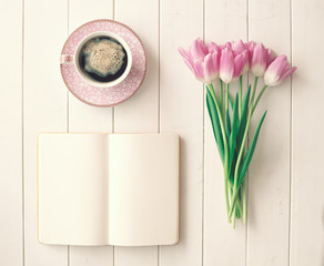 Pink tulips, coffee cup and notebook over white wood