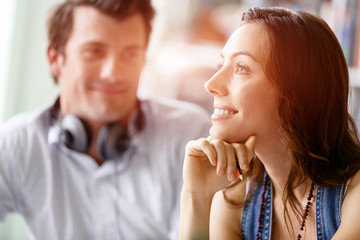 Young pretty woman smiling with man on background
