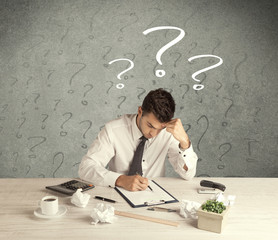 Businessman at desk with question mark