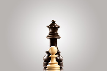 Rivalry / Leadership and bravery concept; white wooden single pawn staying against a black queen.