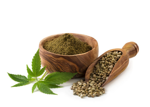 Hemp seeds and flour with a green leaf on a white background