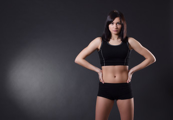 Fitness woman standing against black background