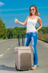 positive woman hiker with big suitcase on the road
