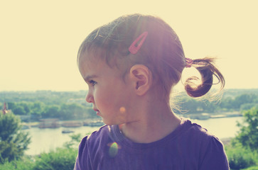 Profile of a little dark haired girl with pony tail, on a sunny day. Image filtered in faded, washed out, retro, vintage, Instagram style with lens flare.
