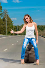 Girl shooting with a suitcase on the road car