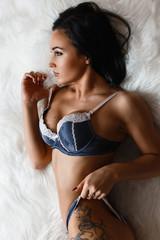 Fashionable young brunette sensual woman with stylish tattoo  lying