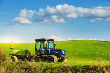 Tractor on tracks in the summer sunny day on a green field.