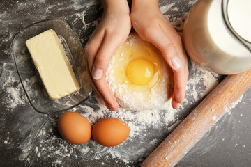 Female hands making dough, top view