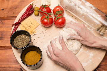 Female hands make a pizza dough. On a wooden Board are the ingredients for the pizza: tomatoes, cheese, basilic, olives.