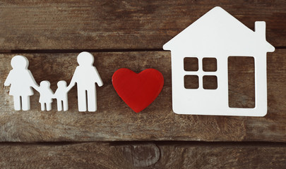 Family figure with a house on wooden  background