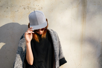 Female model wearing a black blank cap and sunglasses looking away.  Portrait of a young