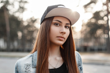 Close-up portrait of a beautiful hipster girl in a black cap