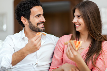 Couple eating pizza on the sofa