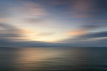 Beautiful vibrant sunrise landscape over calm sea wtih blur filt