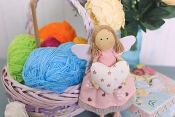 Doll with a heart in a hands and a basket with balls for knitting, flowers, gift box