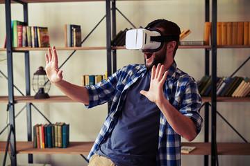 Man having fun using white virtual reality glasses