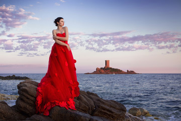 Junge Frau im schönen roten Fashion Kleid am Meer in St. Raphael Frankreich