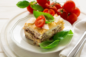 Homemade lasagna with bechamel sauce decorated basil leaves and cherry tomatoes on white plate