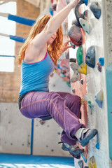 Redhead Woman Indoor Rock Climbing. Female Bouldering Free Climbing