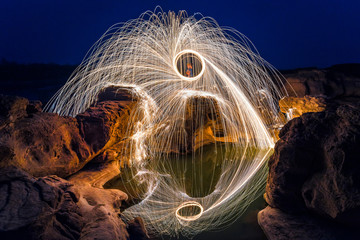 Long exposure capture of Burning steel wool being spun before dusk on a grand canyon rock field of Thailand