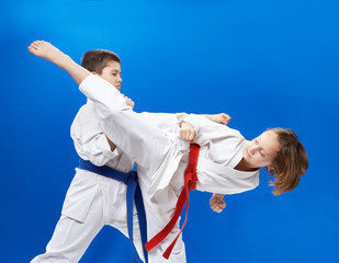Girl and boy in karategi are training karate blows