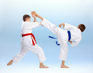 High kick and block are training boys in karategi