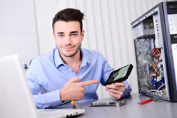 handsome young computer technician repairing desktop computer