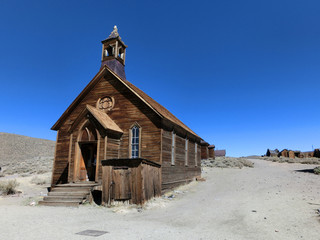 Old vintage weathered wooden church exterior in Bodie, California old west - landscape color photo