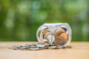 Thai baht coins spilling out of money jar, selective focus