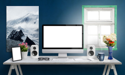Computer display on office desk. Isolated, white screen for mockup. Creative modern desk with speakers, picture frame, glasses, keyboard, mouse, flowers, cup of coffee. Art canvas on blue wall