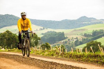 Front View of a Young Man With Bicycle on unpaved beautiful road