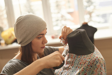 The seamstress cuts the fabric on a mannequin scissors in the Studio