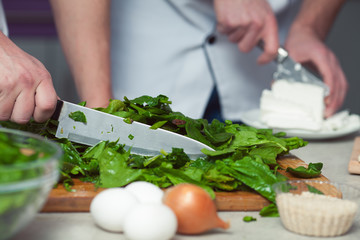 Vegetarian bakery concept. Chef's hands cutting feta cheese, spinach