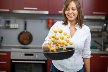 Young smiling woman, cooking potatoes in a wok pan in her kitchen.