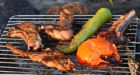 Ribs, green sweet pepper and tomato cooking on the grill over coals