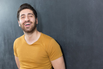 Smiling casual man close up portrait against dark background.