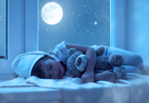 child little girl sleeping at window dreaming and admiring the s