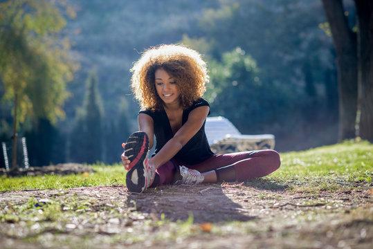 Fitness black woman runner stretching legs after run