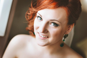 portrait of red-haired young woman bride, smiling, looking at the camera