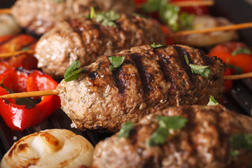 Turkish kebab with vegetables macro on a grill pan. horizontal