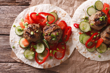 Grilled meat balls with fresh vegetables on a flat bread closeup. horizontal top view