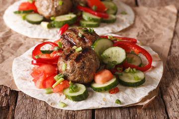 Grilled meat balls with fresh vegetables on a flat bread close up. horizontal