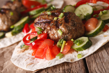 Meatballs with fresh vegetables on a tortilla close-up. horizontal