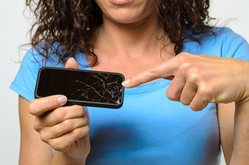Close up of woman holding broken mobile phone