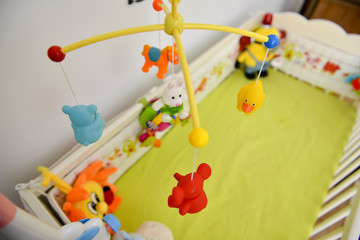 Baby cot with colorful toys hanging