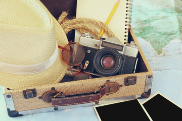 traveling concept. camera, cup of coffee, sunglasses, fedora hat and notebook. vintage style filtered. selective focus